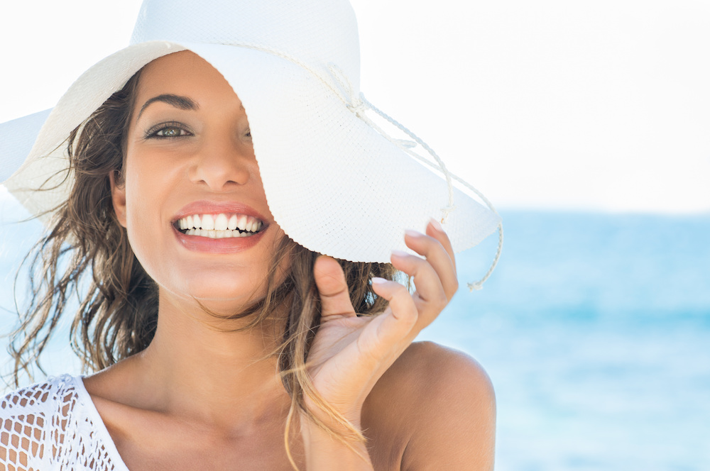Closeup Of Smiling Beautiful Young Woman At Beach With Straw Hat